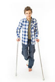 Teenage Boy with crutches and a bandage on his right leg. Isolated against white Stock Photography