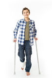 Teenage Boy with crutches and a bandage on his right leg. Isolated against white Stock Image