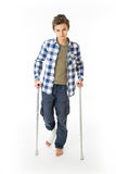 Teenage Boy with crutches and a bandage on his right leg Royalty Free Stock Photography