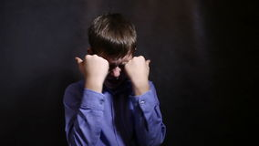 Teenage boy crying upset closed eyes with his. Hands in a blue shirt, studio  background stock video footage