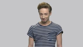 Teenage boy with cunning expression. Portrait of caucasian cunning teen boy wearing striped t-shirt against gray background. Young man having a plan stock video