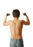 Teenage boy doing exercises with dumbbells. Stock Photo