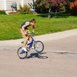 Teenage boy doing tricks on a BMX bike. A teenage boy does wheel hops andpeg stands along with other tricks on a BMX bike Royalty Free Stock Photography