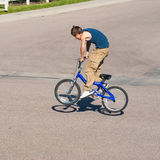 Teenage boy doing tricks on a BMX bike. A teenage boy does wheel hops andpeg stands along with other tricks on a BMX bike royalty free stock image