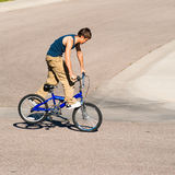 Teenage boy doing tricks on a BMX bike. A teenage boy does wheel hops andpeg stands along with other tricks on a BMX bike Stock Images