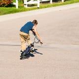 Teenage boy doing tricks on a BMX bike. A teenage boy does wheel hops andpeg stands along with other tricks on a BMX bike Stock Photo