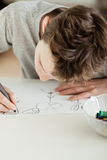 Teenage Boy Draw Something on White Paper Royalty Free Stock Photos