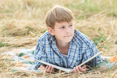 Teenage boy dreaming reading book Stock Image