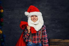 Teenage boy dressed in Santa`s holiday costume. royalty free stock images
