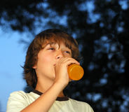 Teenage Boy Drinking Orange Drink. From a glass bottle with dark skies in the background Stock Images