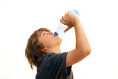 Teenage Boy Drinking Water. From a plastic bottle isolated on white background Royalty Free Stock Photography