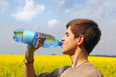 Teenage Boy Drinking  Water. Teenage boy drinking mineral water from plastic bottle with a blank label on a sunny day in the field Royalty Free Stock Photo