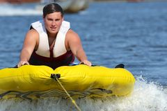 Teenage Boy Eager to Get His Tubing Run Started. Teenage boy pulling up out of the water at the start of his tubing run Royalty Free Stock Photos