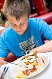 Teenage boy eating Royalty Free Stock Image