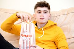 Teenage boy eating popcorn stock photo