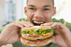 Teenage Boy Eating Sandwich Royalty Free Stock Images