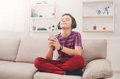 Teenage boy enjoying music in headphones at home Stock Image