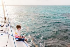 Teenage boy on board of sailing yacht. Teenage boy enjoying sailing on board a chartered catamaran or yacht royalty free stock photos