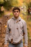 Teenage boy and falling leaves royalty free stock photo