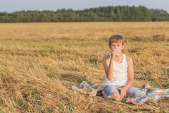 Teenage boy in farm field having break Stock Images