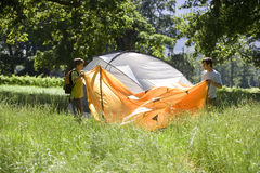 Teenage boy (13-15) and father assembling tent in woodland clearing, side view Royalty Free Stock Image
