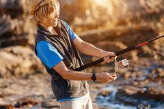 Teenage boy fishing at sea. Teenage boy fishing with rod at sea royalty free stock photography