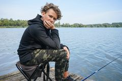 Portrait of a teenage boy fishing on the bank of the river or lake. Cute boy with curly hair royalty free stock images