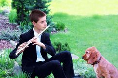 Teenage Boy with Flute and Dog. Teenage boy street musician playing the flute in the park. Dog sitting in front of and listening to music Stock Photos