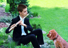 Teenage boy with Flute and Dog. Teenage boy street musician playing the flute in the park. Dog sitting in front of and listening to music Stock Images