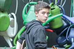 Teenage boy in front of hanging watering cans Royalty Free Stock Photography
