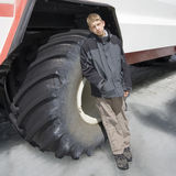 Teenage boy in front of a large tire Royalty Free Stock Image