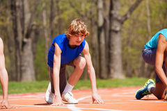 Teenage boy getting ready for race on the track. Portrait of young runner, teenage boy in sportswear, getting ready for race on stadium's track royalty free stock photos