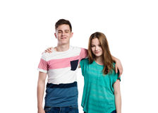 Teenage boy and girl, arms around each other, isolated. Stock Photos