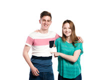 Teenage boy and girl, arms around each other, isolated. Royalty Free Stock Photography