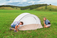 Teenage boy and girl arranges tourist tent Royalty Free Stock Photo