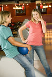 Teenage boy and girl in a bowling alley, flirting and exchanging phone numbers Stock Photos