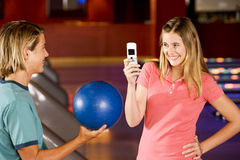 Teenage boy and girl in a bowling alley, girl taking a picture Stock Photos