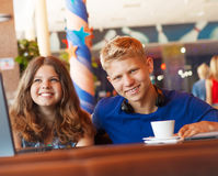 Teenage boy and girl in cafe. Cheerful teenage couple spend time in cozy cafe Stock Photography