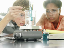 Teenage boy and girl (15-17) doing science experiment at desk in classroom, surface level Stock Photos