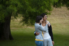 Teenage boy and girl embrace in park Stock Photography