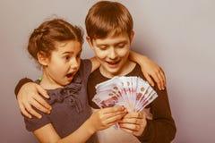Teenage boy and girl holding money bills  Stock Image