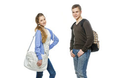 Teenage boy and girl isolated on white. Beautiful teenage girl and boy in casual clothes with school bags standing over white background. Isolated. Copy space Royalty Free Stock Photo