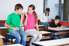 Teenage Boy And Girl Listening Music In Classroom. Teenage boy and girl looking at each other while listening music on mobilephone in classroom Stock Images