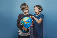 Teenage boy with a girl looking at a globe girl Royalty Free Stock Images