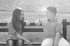 Teenage boy and girl in love sitting on bench in summer park Royalty Free Stock Photo