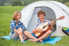 Teenage boy and girl near the tent playing a guitar outdoors Stock Images