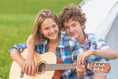 Teenage boy and girl near the tent playing a guitar outdoors Royalty Free Stock Photos