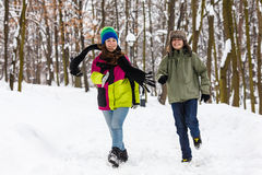 Teenage boy and girl running outdoor in winter park Royalty Free Stock Image