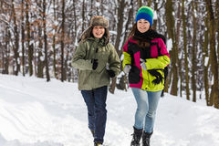 Teenage boy and girl running outdoor in winter park Stock Image