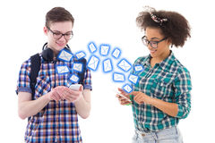 Teenage boy and girl sending sms messages each other isolated on Royalty Free Stock Photos